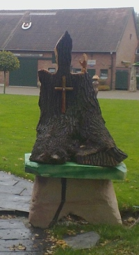 A tree trunk on a pedestal with a carved wood hand and a cross. Photo: PK Read