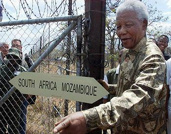Nelson Mandela opens a gate between South Africa and Mozambique, creating a corridor for elephants to freely cross transnational boundaries. Photo: Tony Weaver / PPF