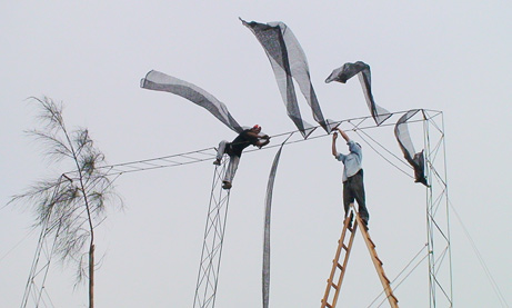 Two workers in Bellavista, Peru, perched 18 feet (5.5 meters) high to sew nets onto a fog-collecting apparatus (2007) Photo: Anne Lummerich / Nat Geo