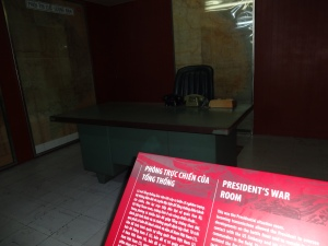 The President's War Room, a small desk, a couple of old telephones, a few yellowing maps on the walls, all located several stories below the Palace in a concrete bunker.