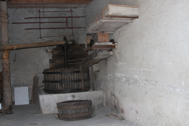 The pressing barn. Apples would be loaded on the ramp to the right, rolled down into the press and onto a small bed of straw. Once the press vat was loaded, weights were placed atop the apples and pressed through the fine straw, into the juice vat at the front. The turning was all done by hand, usually two or three family members turning the large pole to the left. Photo: PK Read